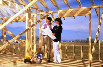 Photo of Couple looking at set of plans in their framed home