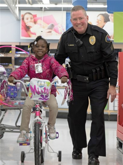 Child Riding a bike with a cop while they shop